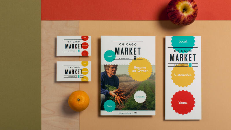 Chicago market business cards, booklet and flyer arranged on a surface with an apple and orange