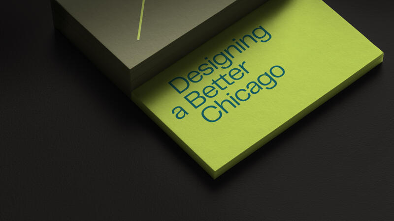 A stack of Designing a Better Chicago business cards using the colors lime and olive green