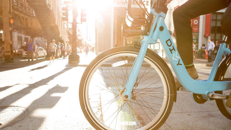 Divvy bike with rider in downtown Chicago