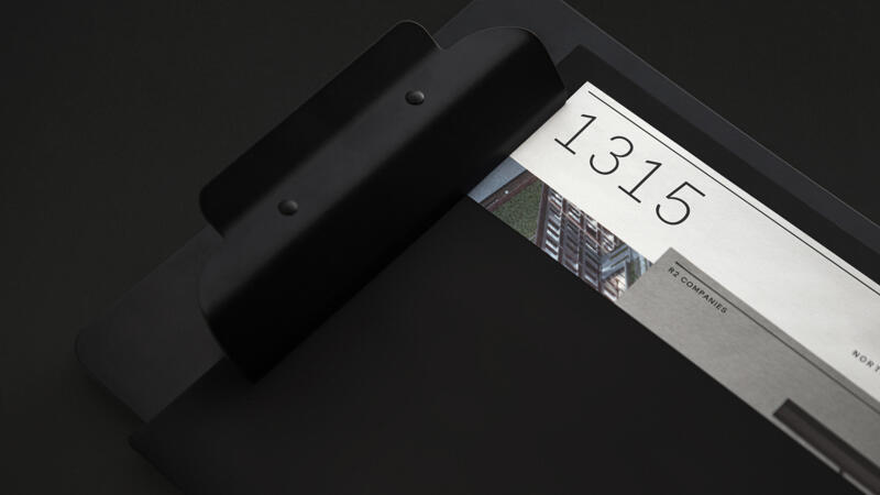 Black clipboard with black folder and designed pages featuring custom R2 font numbers