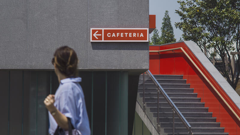 "Wayfinding signage affixed to a concrete wall that reads ""Cafeteria"" with a person walking by"