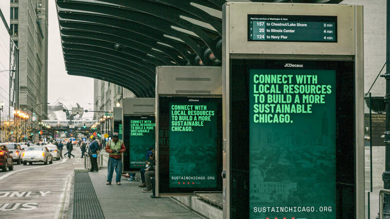 Series of four downtown bus stop signs that say connect with local resources to build a more sustainable chicago.