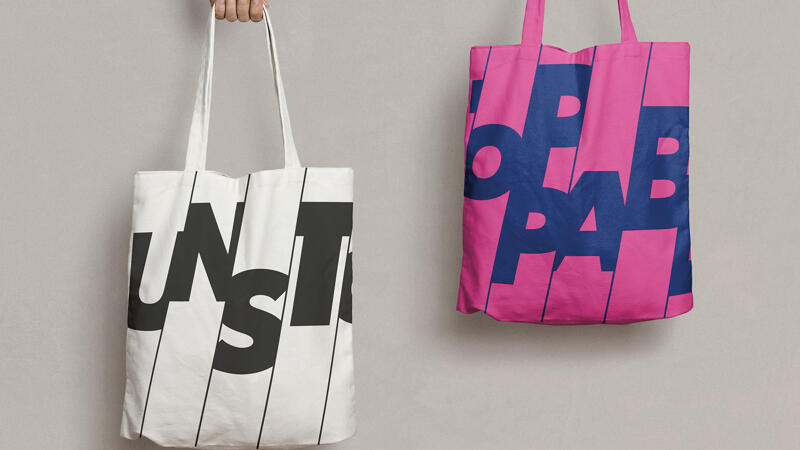 Two tote bags with the cropped unstoppable logo printed on the front. One bag is white one bag is pink