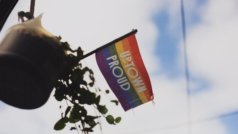 Small rainbow flag flying against a blue sky that reads Uptown Proud