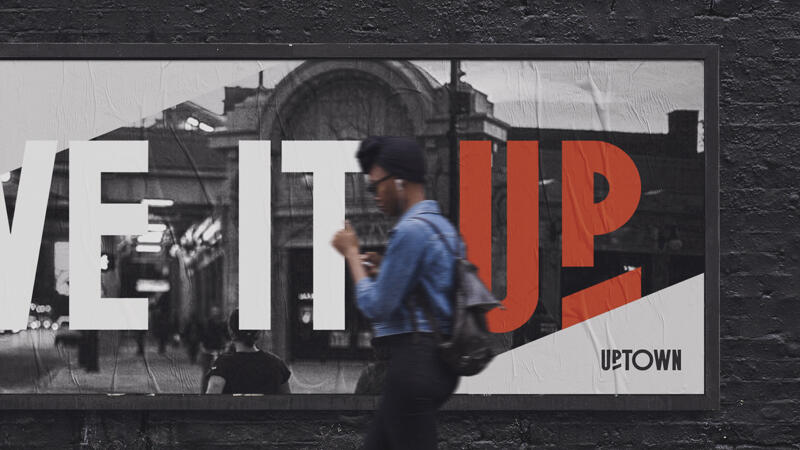 """Woman walking in front of billboard featuring Uptown logo and campaign message """"Live it Up"""""""