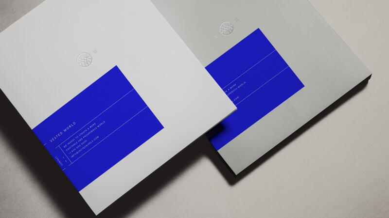 Vested World stationery and booklets featuring logo and brand colors